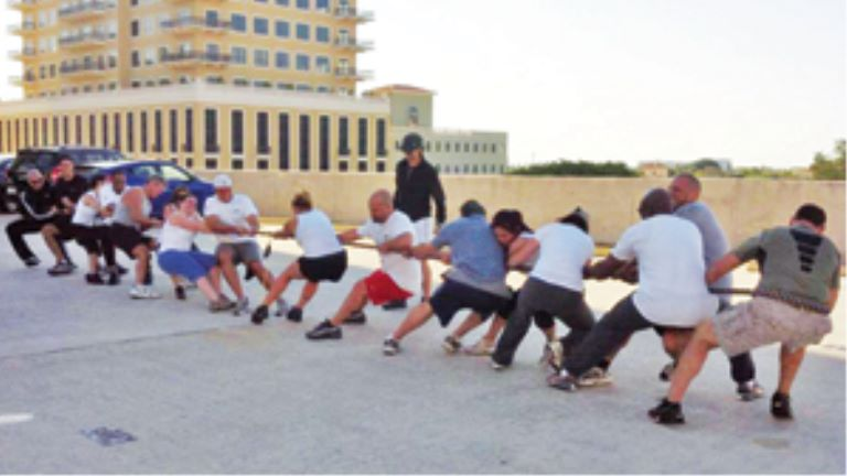 adults playing tug of war on building rooftop