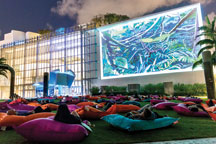 people sitting outside on large cushions watching a movie projected on a building