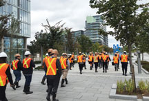 people waling with hard hats and vests